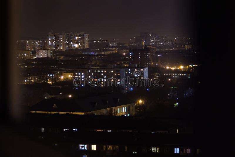 An apartment building at night. Residential flats windows lighting up and turning off overnight. Night view of the neighbourhood with high-rise apartment stock photography