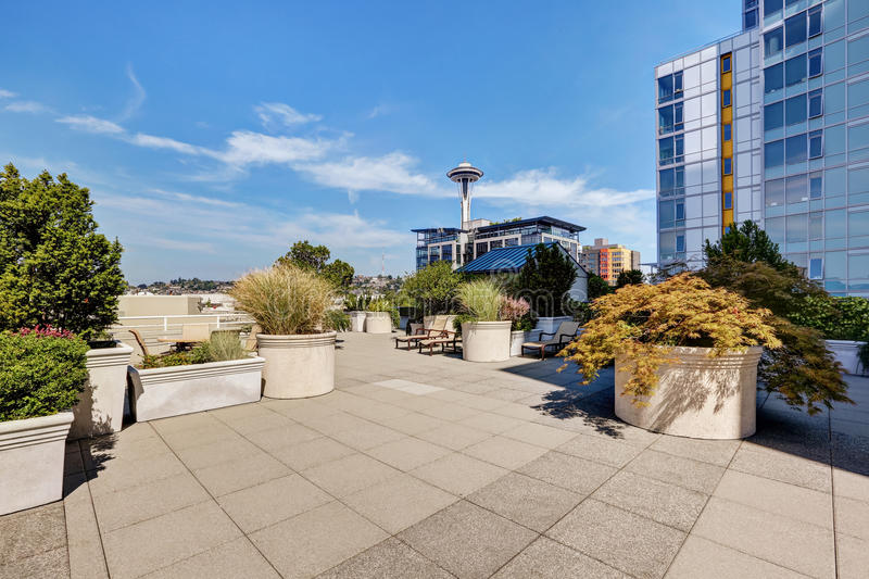 Apartment building roof top terrace exterior with lounge chairs. And lots of greenery. Northwest, USA royalty free stock photo