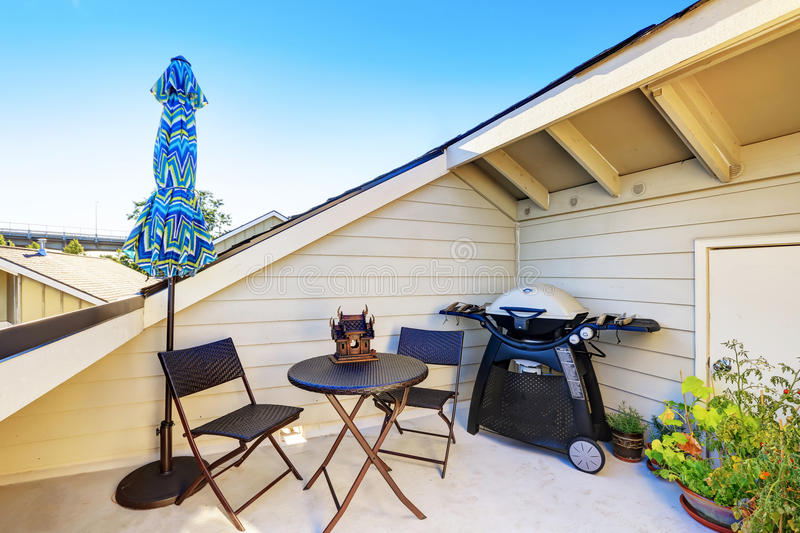 Apartment building roof top terrace exterior. Apartment building roof top terrace exterior with patio table set and barbecue. Northwest, USA royalty free stock photography