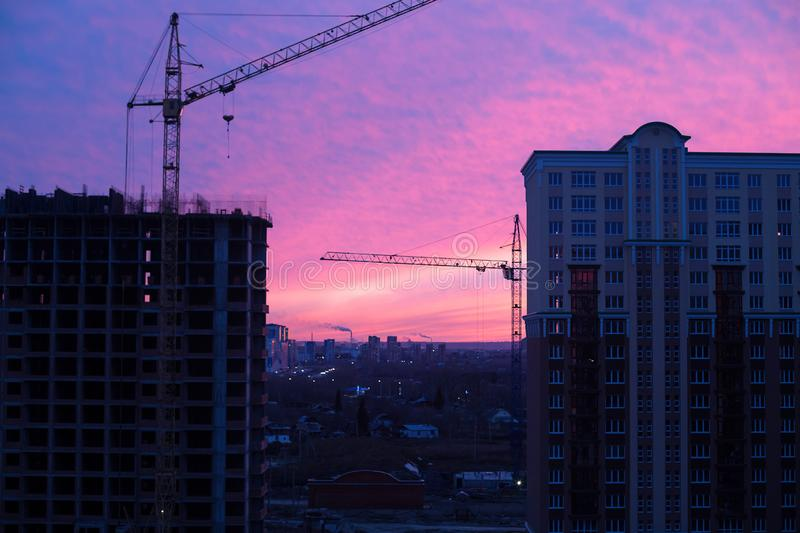 Apartment building site and crans in the city in sunrise royalty free stock photography