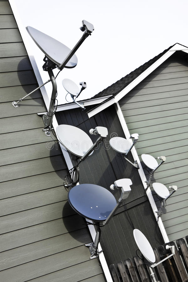 Apartment Eight TV Satellite Dishes Tilted. These apartments each have their own TV satellite dish. Most are mounted on the edge of the building stock photography