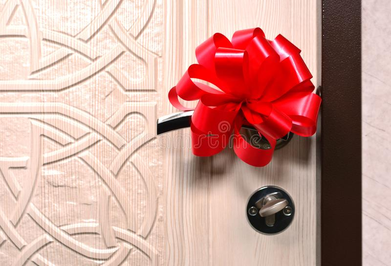 Apartment for a gift concept with front door handle and big red bow. Gift house royalty free stock images