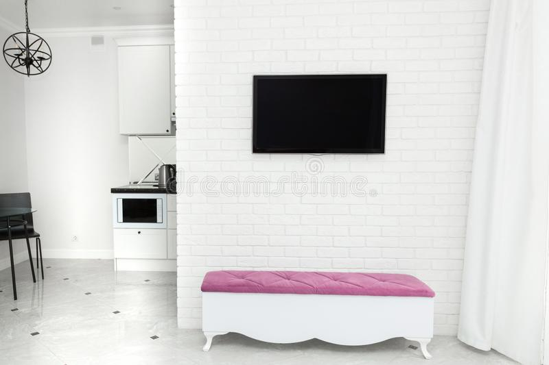 Apartment interior in modern light style. TV on the wall and a bench with a color accent. Apartment interior in modern light style. TV on the wall and a bench royalty free stock images