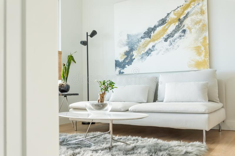 Apartment living room angle view, with white furniture and modern interior design, and some house plants. Futon couch, coffee royalty free stock photo