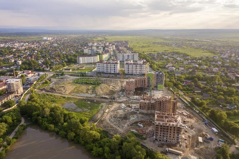 Apartment or office brick buildings under construction, top view. Building site with tower cranes from above. Drone aerial. Photography stock photo
