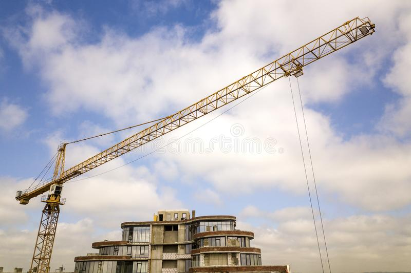 Apartment or office tall building under construction. Brick walls, glass windows, scaffolding and concrete support pillars. Tower royalty free stock image