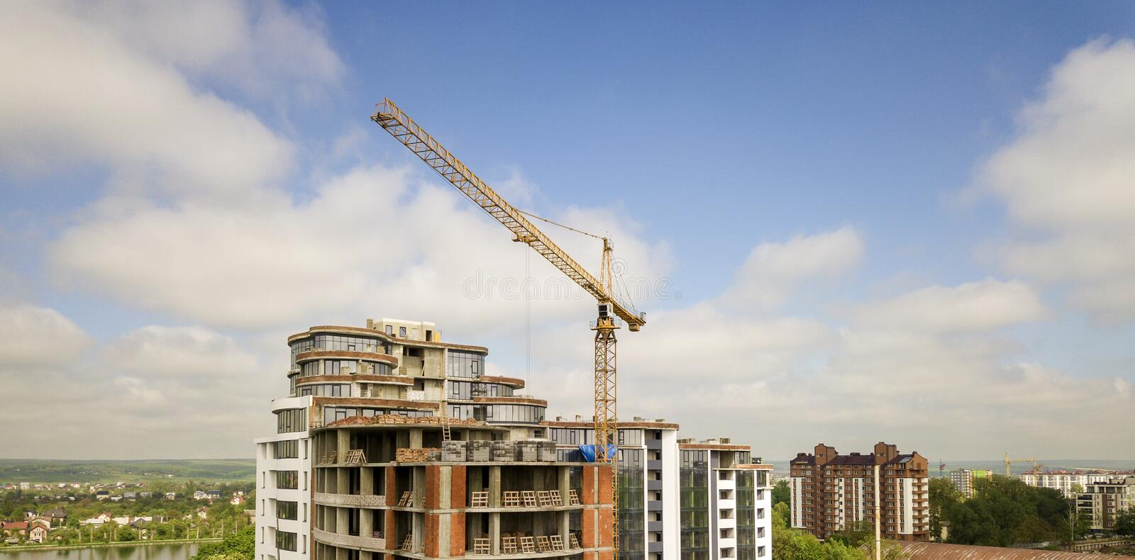 Apartment or office tall building under construction. Brick walls, glass windows, scaffolding and concrete support pillars. Tower. Crane on bright blue sky copy royalty free stock photography