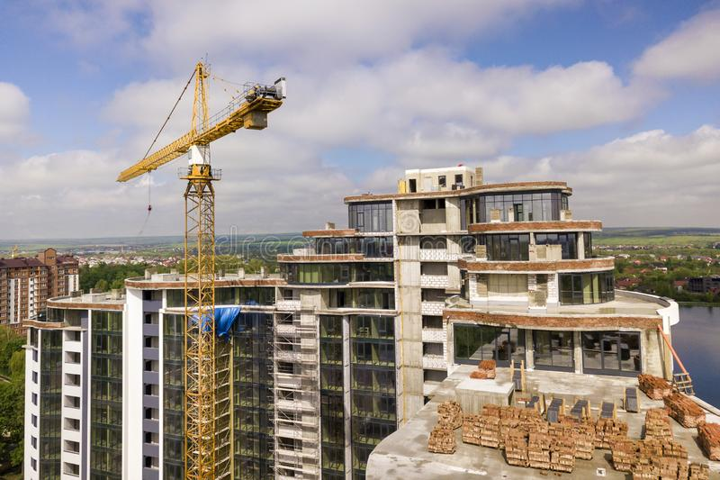 Apartment or office tall building under construction. Brick walls, glass windows, scaffolding and concrete support pillars. Tower. Crane on bright blue sky copy royalty free stock image