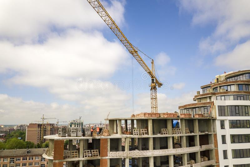 Apartment or office tall building under construction. Brick walls, glass windows, scaffolding and concrete support pillars. Tower. Crane on bright blue sky copy royalty free stock photos