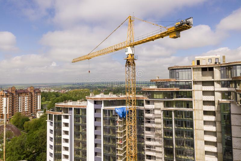 Apartment or office tall building under construction. Brick walls, glass windows, scaffolding and concrete support pillars. Tower. Crane on bright blue sky copy stock image