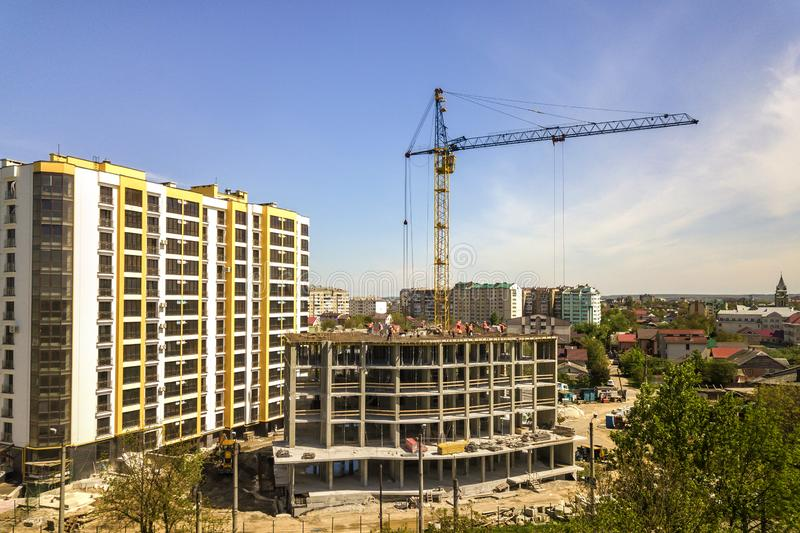 Apartment or office tall building under construction. Working builders and tower cranes on bright blue sky copy space background stock images