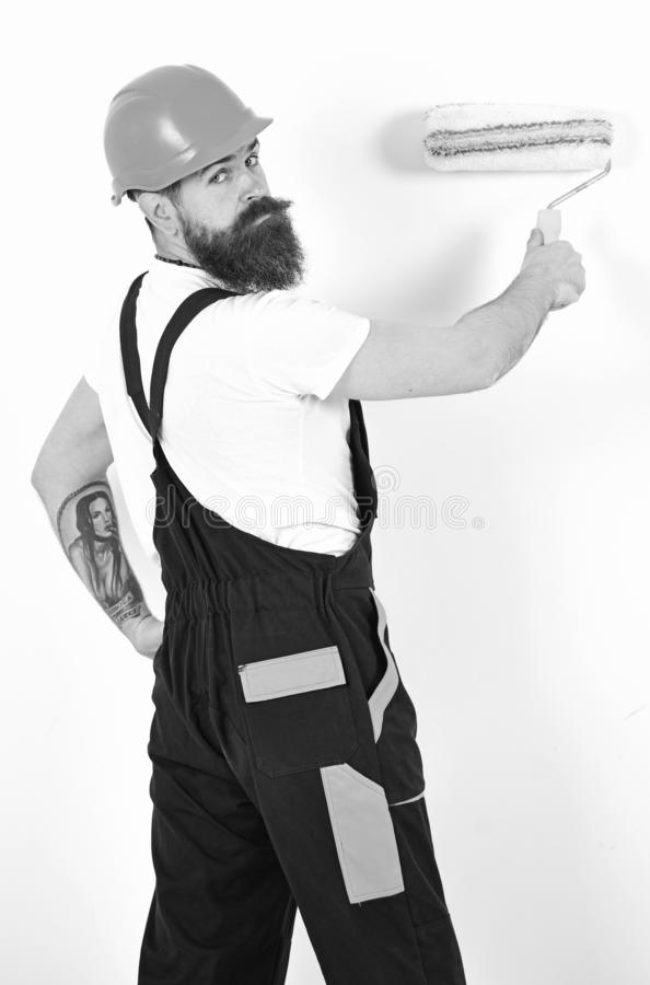 Apartment redecoration. Turn back painter with paint roller in front of white wall. Isolated bearded man with tattoo on stock image