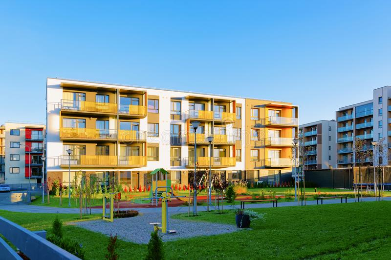 Apartment residential house facade architecture and kids playground. And outdoor facilities. Blue sky on the background stock image