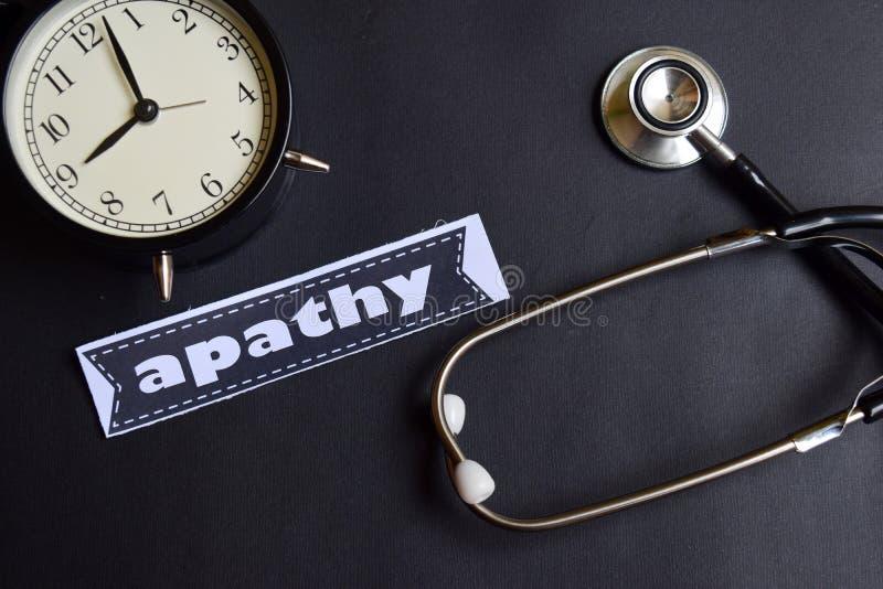 Apathie auf dem Papier mit Gesundheitswesen-Konzept-Inspiration Wecker, schwarzes Stethoskop lizenzfreie stockbilder