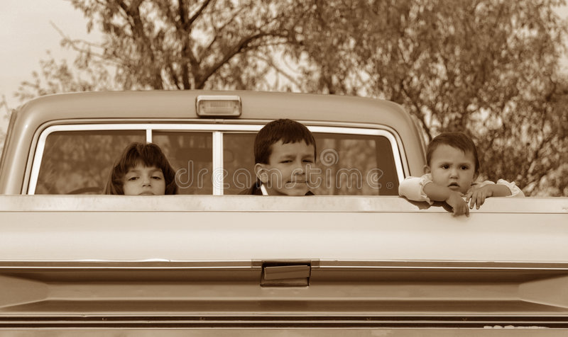 Apathy Kids. Three Hispanic American children, each with their own possibly bored expression, in the back of a classic pick up truck. Sepia toned for effect. If stock images
