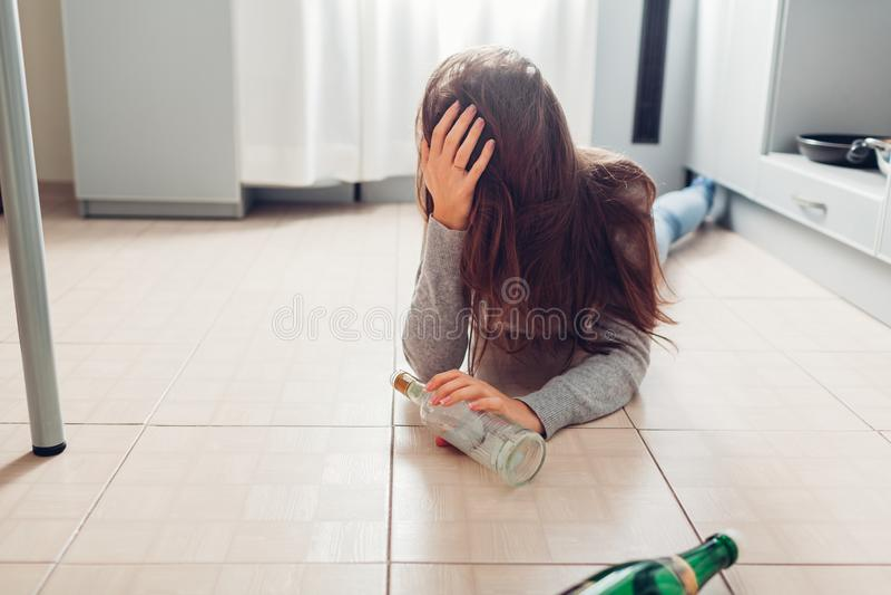 Apego de álcool fêmea A jovem mulher acordou no assoalho da cozinha após o partido cercado com garrafas de vinho hangover imagens de stock royalty free