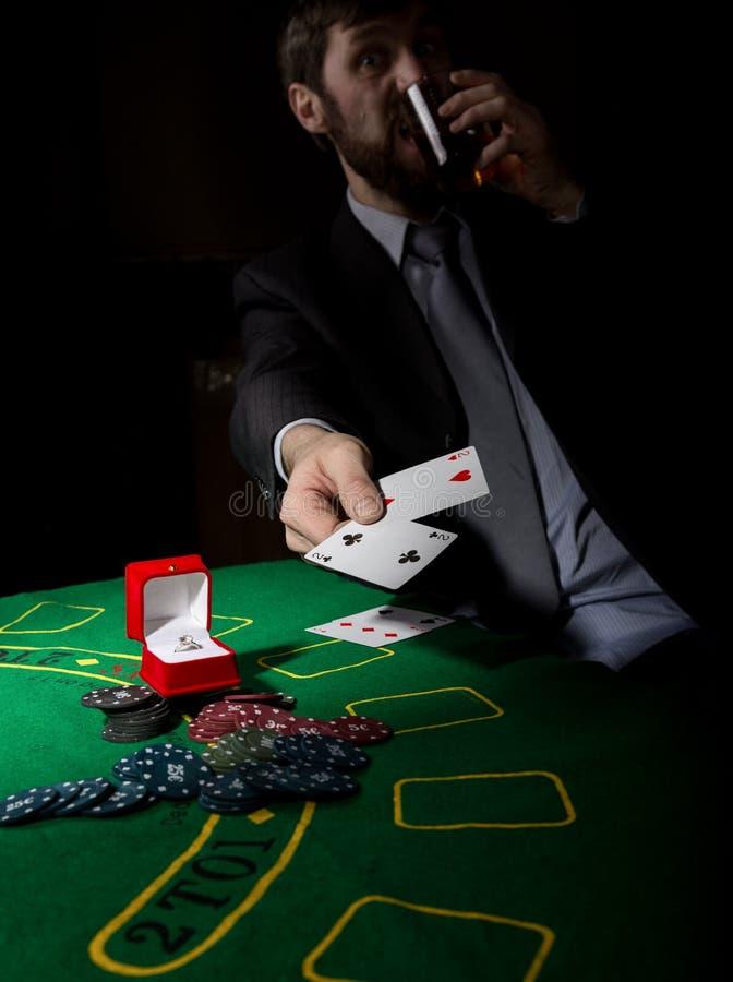Apego de jogo homem em uma aguardente bebendo do terno de negócio e cartões dos lances com combinação perdedora Microplaquetas do foto de stock