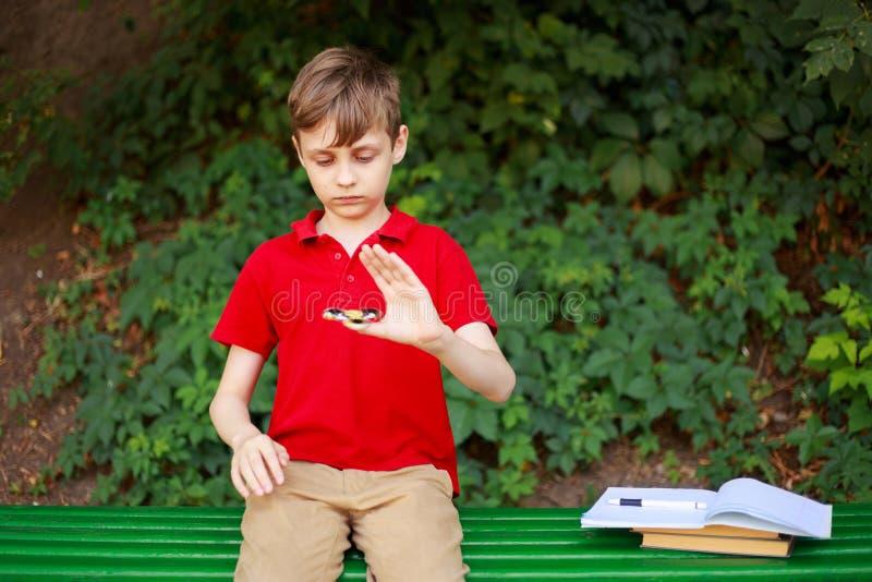 Apego del artilugio Colegial que juega con el hilandero de la persona agitada en lugar de otro imagenes de archivo