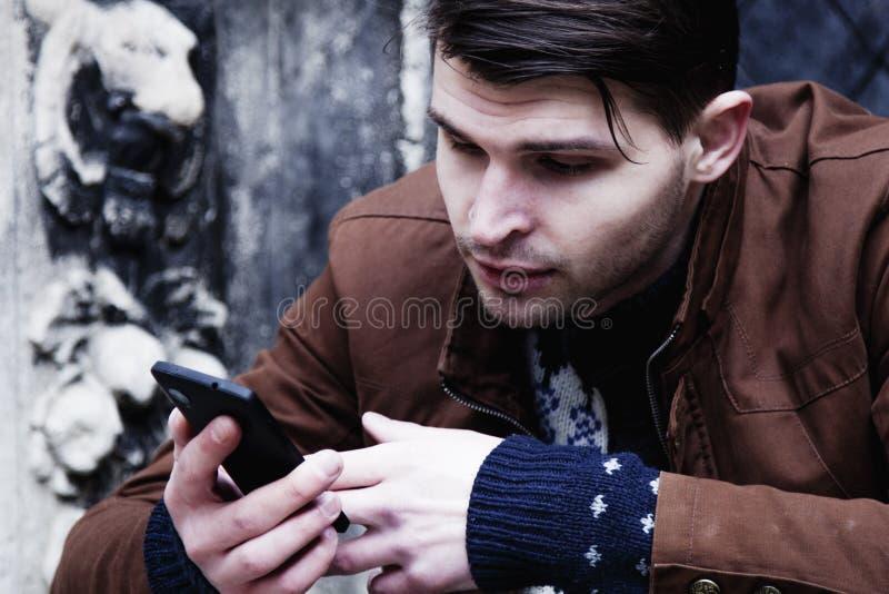 Apego social dos meios homem novo que guarda um psycholo do smartphone foto de stock