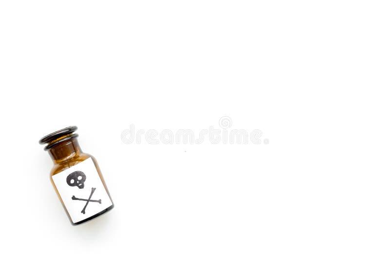 Apegos peligrosos, entretenimiento peligroso veneno Botella con el cráneo y la bandera pirata en la opinión superior del fondo bl imagenes de archivo