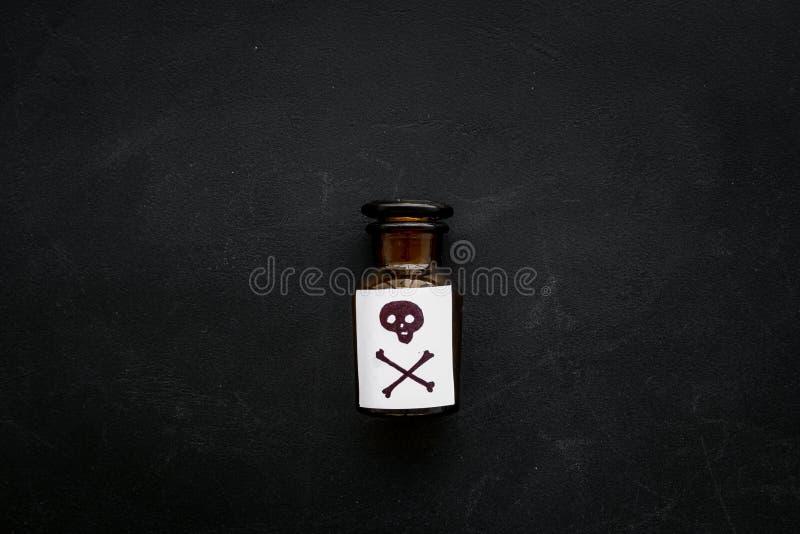 Apegos peligrosos, entretenimiento peligroso veneno Botella con el cráneo y la bandera pirata en la opinión superior del fondo ne imagenes de archivo