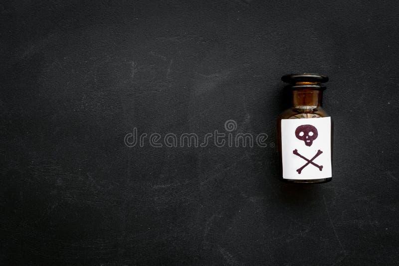 Apegos peligrosos, entretenimiento peligroso veneno Botella con el cráneo y la bandera pirata en la opinión superior del fondo ne imagen de archivo