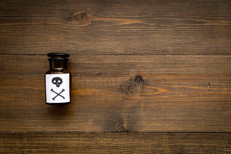 Apegos peligrosos, entretenimiento peligroso veneno Botella con el cráneo y la bandera pirata en el top de madera oscuro del fond foto de archivo