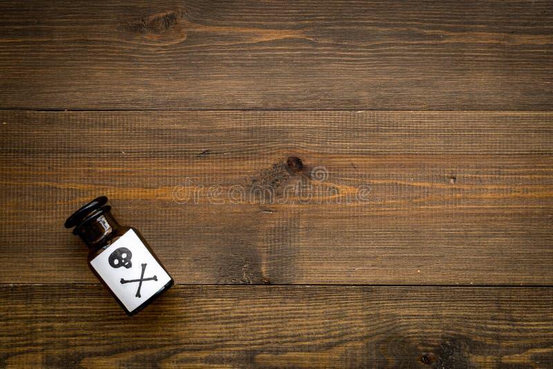 Apegos peligrosos, entretenimiento peligroso veneno Botella con el cráneo y la bandera pirata en el top de madera oscuro del fond imagen de archivo