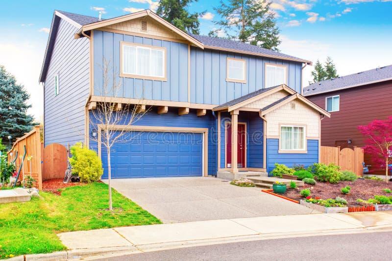 Apelação agradável do freio da casa azul com jardim dianteiro e da garagem com entrada de automóveis imagem de stock