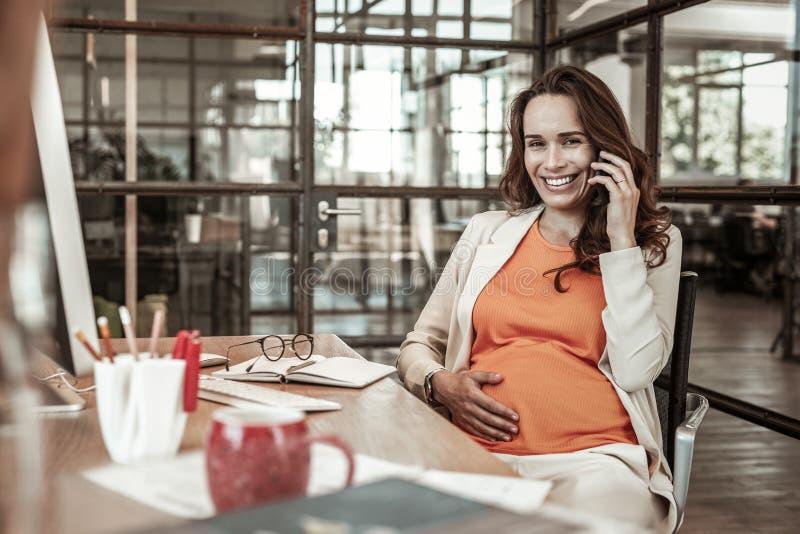 Apelando a mulher trabalhadora que tem o sorriso largo ao falar imagem de stock royalty free