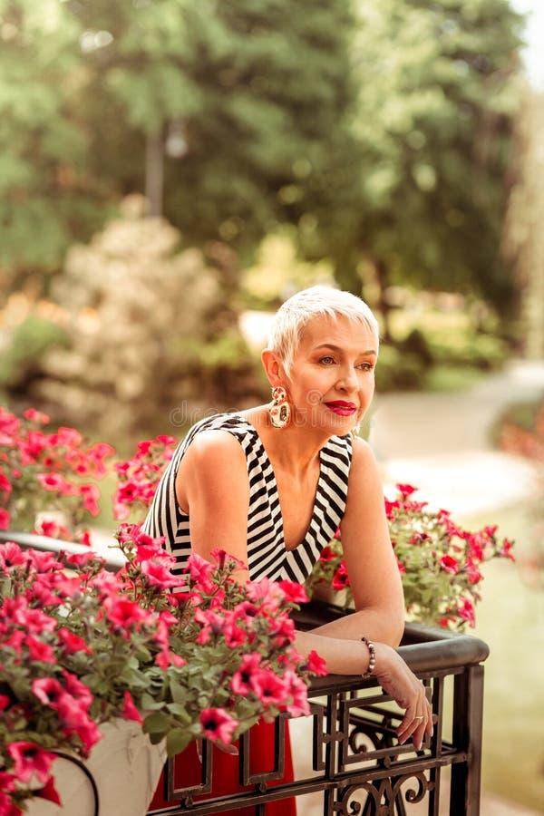 Apelar la situación pensativa de la sensación elegante madura de la mujer en balcón imagenes de archivo