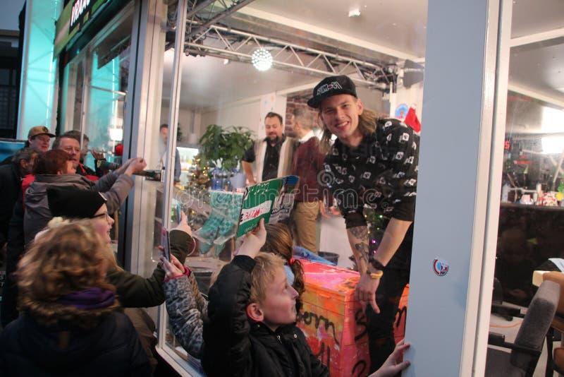 Apeldoorn, Países Baixos - 23 de dezembro de 2017: O ` s de 3 DJ do rádio do NPO 3FM é fechado acima na casa do vidro aumentar mo fotografia de stock