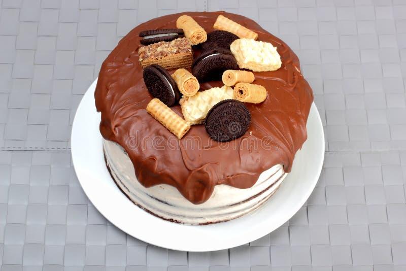 Apelmácese, esmaltado con el chocolate con leche y adornado con las galletas y fotos de archivo libres de regalías