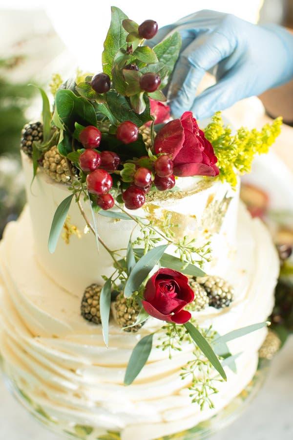 Apelmace al decorador que pone los toques finales en un pastel de bodas fotos de archivo libres de regalías
