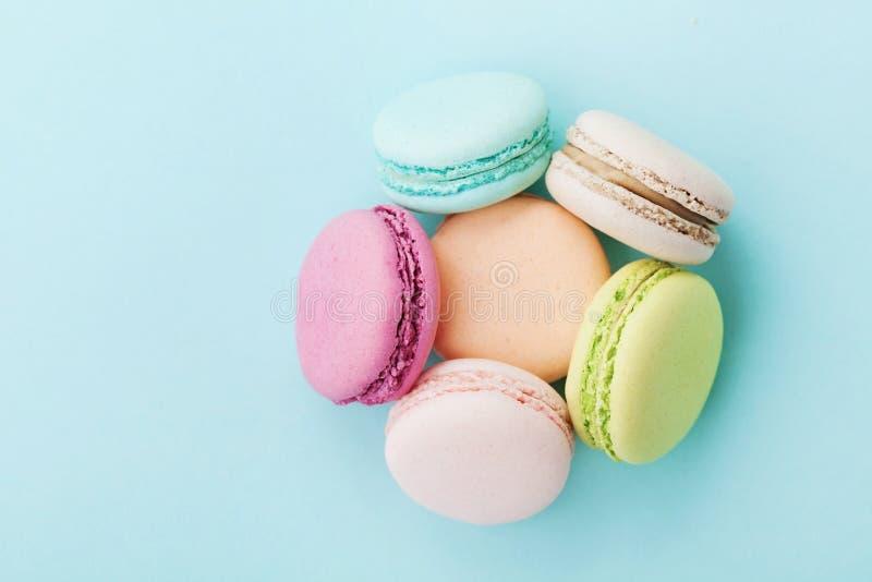 Apelmace el macaron o los macarrones en fondo de la turquesa desde arriba, las galletas de almendra, colores en colores pastel imagen de archivo
