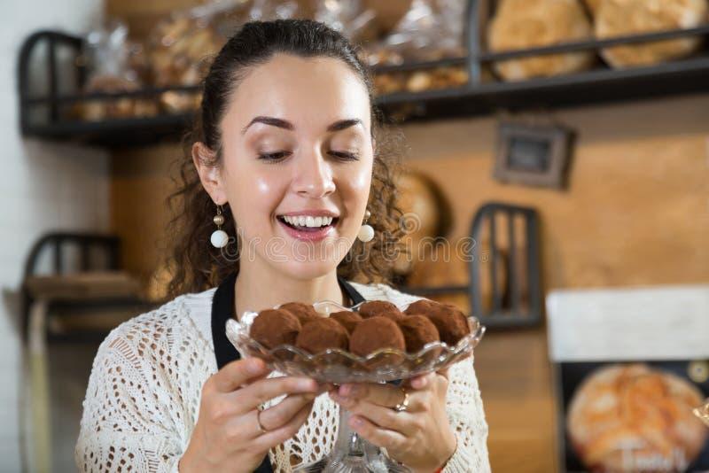 Apelmaza a la mujer del vendedor con las trufas de chocolate deliciosas imagen de archivo libre de regalías