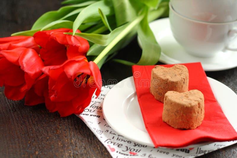 Apelmaza las trufas con los tulipanes rojos fotografía de archivo libre de regalías