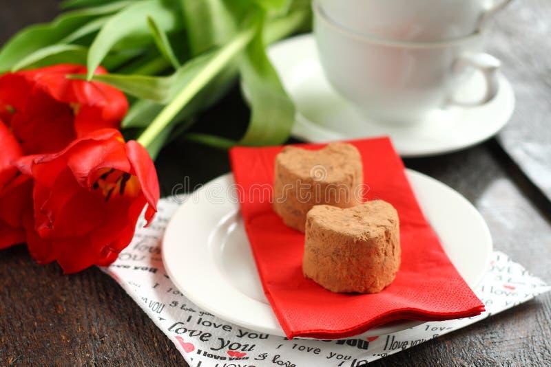 Apelmaza las trufas con los tulipanes rojos foto de archivo
