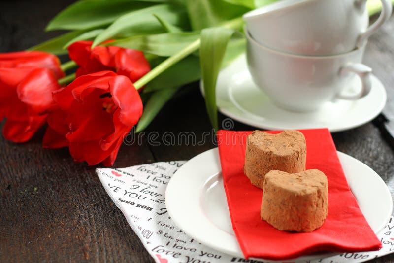 Apelmaza las trufas con los tulipanes rojos foto de archivo libre de regalías
