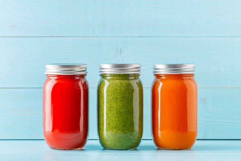 Apelsin/gräsplan/röda kulöra smoothies/fruktsaft i en krus arkivfoto