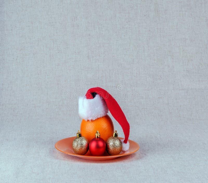Apelsin i ett lock av Santa Claus royaltyfria foton