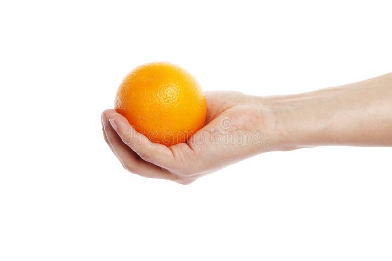 Apelsin i handen som isoleras på en vit bakgrund arkivfoto