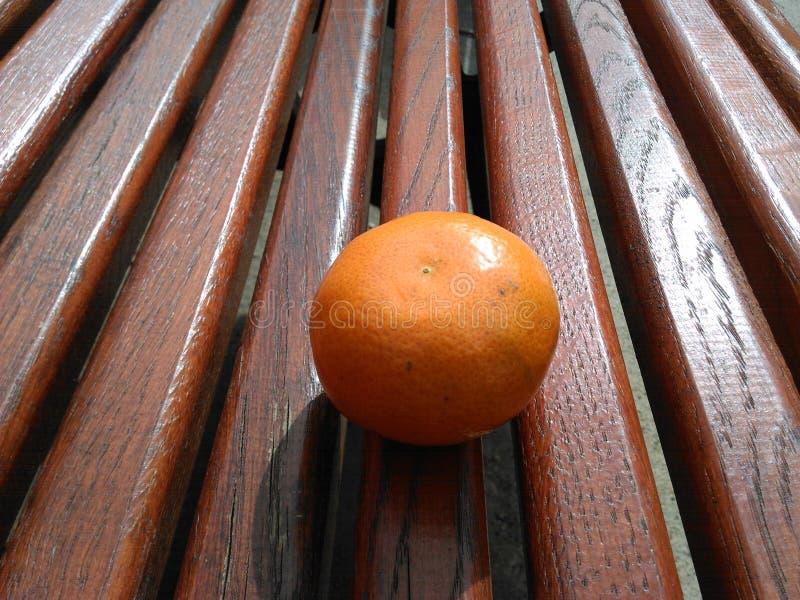 Apelsin och bänk fotografering för bildbyråer