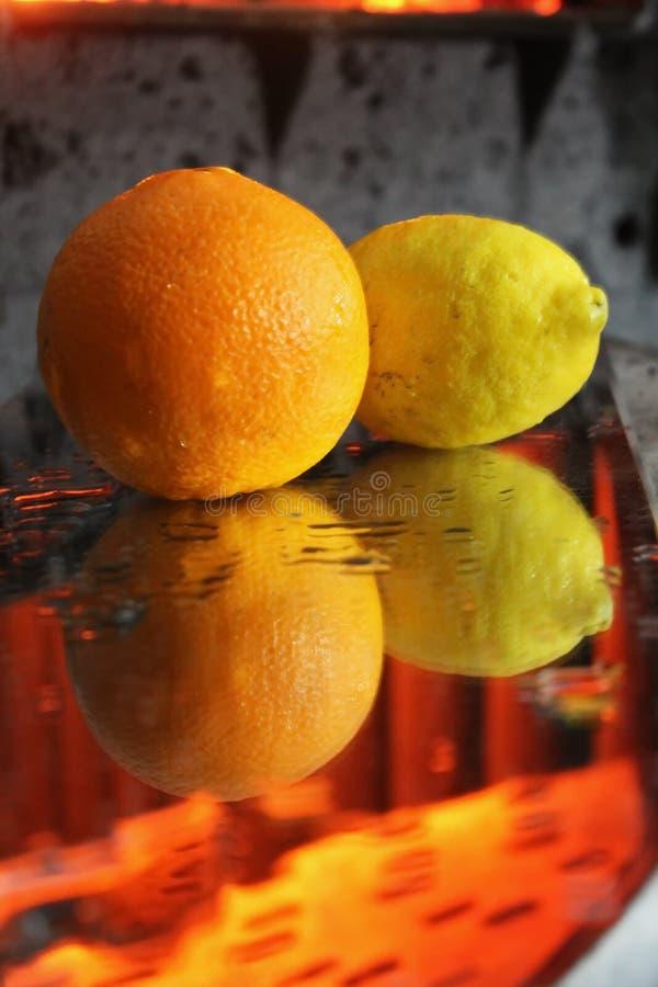 Apelsin och citron i vatten i ljust ljus fotografering för bildbyråer