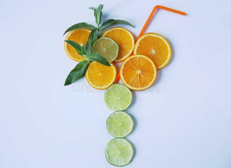 Apelsin och limefrukt som skivas in i cirklar som ut läggas i form av ett exponeringsglas med ett dricka sugrör med mintkaramells arkivbild