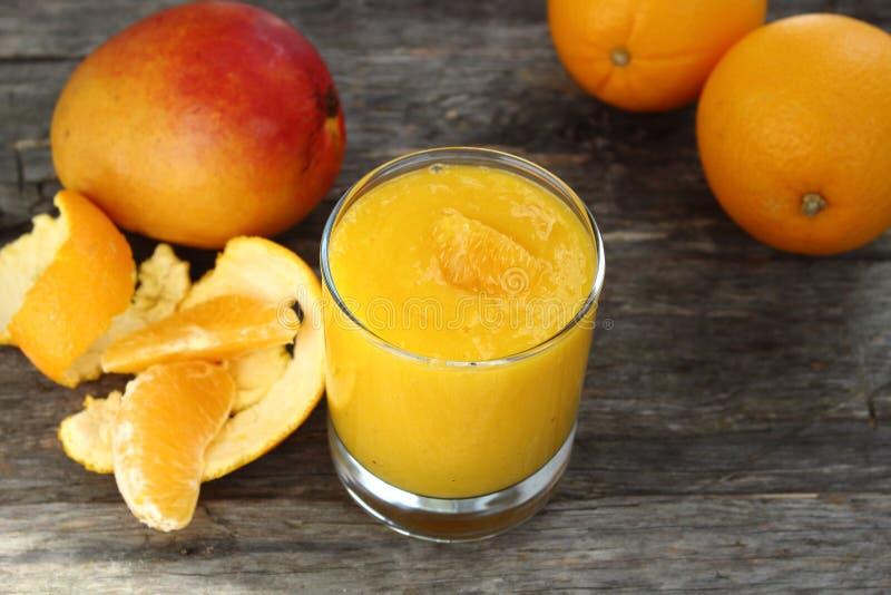 Apelsin- och mangosmoothie arkivfoton