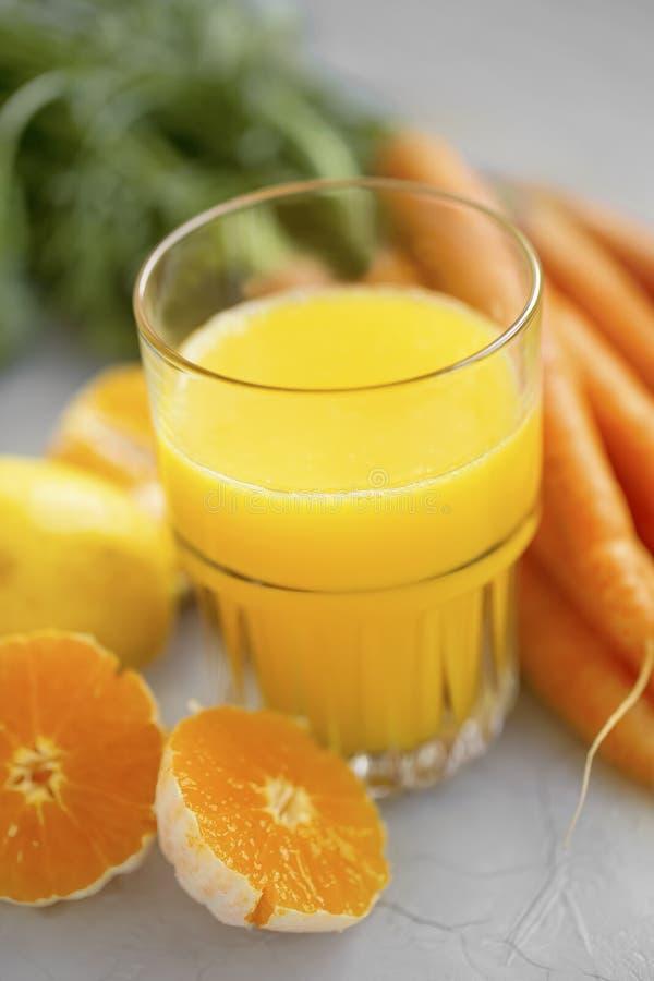 Apelsin och morotfruktsaft arkivfoton