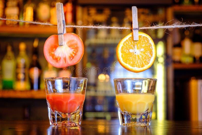 Apelsin- och tomatfrukter med fruktsaft i exponeringsglaset arkivbild