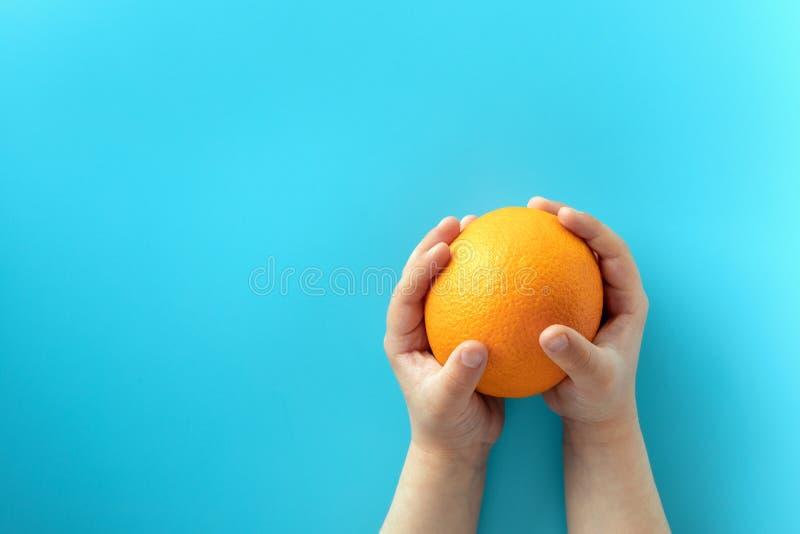 Apelsin p? den bl?a bakgrunden i h?nderna av ett barn ?ta f?r begrepp som ?r sunt royaltyfri fotografi