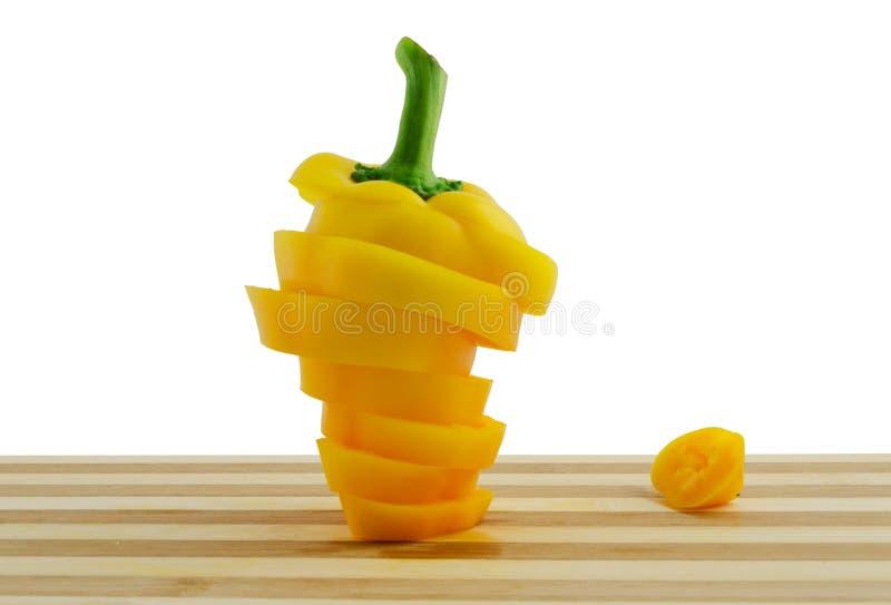 Apelsin skivad peppar på skrivbordet som isoleras på vit arkivbild